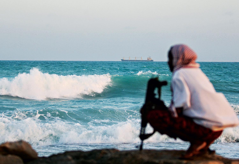 Observado por um pirata somali, um cargueiro grego ancora em Hobyo, nordeste da Somália. Foto: AFP